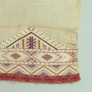 Woven towel with bands of geometric patterning at both ends. One band is seven inches, and the other is two inches.
