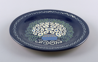 Circular, dark blue background glaze; sgraffito decoration of flowers in vase, with leafy halo; around rim of plate a wavy line with dots.