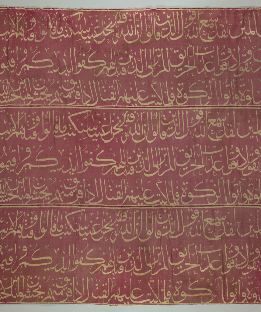 Three identical horizontal panels of ribbed pink silk, each with a double row of Arabic script in white, running parallel with the warps. Lined with heavy white cotton cloth with double thickness at top for hanging.