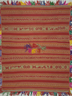 Poncho of wool, tapestry weave, embroidered in striped geometric pattern in shades of red, greys, browns and orange. Fringed on all sides. Tapestry woven bands in same colors as embroidered bands. Woven by the Quechua, Urabamba Valley, near Cuzco, Peru. Bought in 1949.