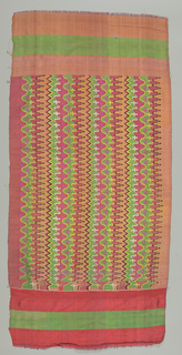 Four pieces sewn together: border of pink silk; narrow multicolored bands in orange, green, red, and purple. Center panel with side border of red and green striped silk. Panel design of geometrical zigzag tapestry in red, pink, gree, yellow, orange, brown, and white. Top border of plain brown cotton.