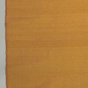 Long hadwoven breath, warm burnt-orange, with thick yellow weft and fine magenta warp, giving changeable effect when crumpled. At one end, an inch-wide band in which fine blue weft replaces the yellow. Silk is from worm of East Thailand which feeds on scrub oak.