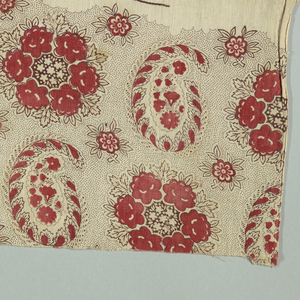 Floral bouquets alternate with paisley botehs in black and red and faded yellow on white.