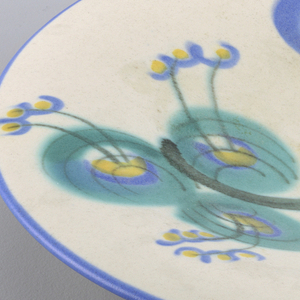 Large circular dish with an oriental style floral design on it in turquoise, purple and yellow on a white background.