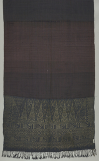 "Long panel, possibly a breast cloth (kemben), made of two wide borders, showing rows of rich gold brocading. Border shows ""tumpal"" motif (row of isosceles triangles) plus stylized floral and vegetable design. Ground woven in dark blue silk, with occasional red silk thread."