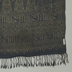 """Long panel, possibly a breast cloth (kemben), made of two wide borders, showing rows of rich gold brocading. Border shows """"tumpal"""" motif (row of isosceles triangles) plus stylized floral and vegetable design. Ground woven in dark blue silk, with occasional red silk thread."""