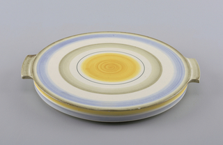 Circular, with two flat projecting handles.  Concentric rings of underglaze in blues, green, yellow.  Sides ringed in yellow, blue.