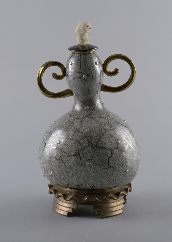 Large gourd-shaped vase (a) having white ground finished with a fine black crackle pattern similar to Raku and larger painted silver toned crackle with synthetic gemstone details; two curled, gold handles opposite eachother at top of neck; base composed of a small circular wavy rim on stepped feet. Small circular gold and black lid (b) with a large white mineral crystal knop.