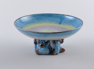 Round bowl with blue, yellow and pink glaze, with allover crazing. Foot in the form of an animal.