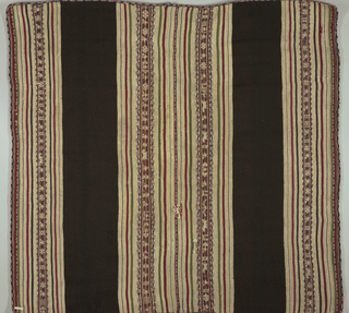 Broad stripes of dark brown and dark red and dull green with warp-patterned geometrical and animal stripes in these colors, on cream ground. Some type of herringbone embroidery in red wool joins two lengths down center. Edged with wool tubular embroidery with lozenge pattern in red, blue and cream.
