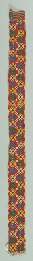 Rectangular piece for a cap with a double row of close-set medium scale floriated crosses in green, yellow, blue, tan and black silks with alternating silver or black centers on a red wool ground.