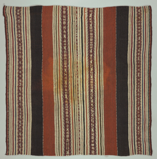 Square made of two lengths seamed down long side. Broad dark brown and rust stripes and brown cream stripes with think stripes of blue and red. Warp-patterned stripes in these colors decorated with animals, flowers, geometrical forms. Double loom cords top and bottom. Elaborate herringbone stitch in brown and blue wool covers center joining.