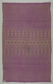 Symmetrical design of deep end borders with small all-over trellis and dot pattern, three narrow geometrical borders above set off by chequered guard stripes and a rectangular central panel into which rise, point to point from the end borders, isoceles triangles; symmetrical arrangement of rosettes in interspaces. Silver on faded purple. Two long selvages with silk wraps.