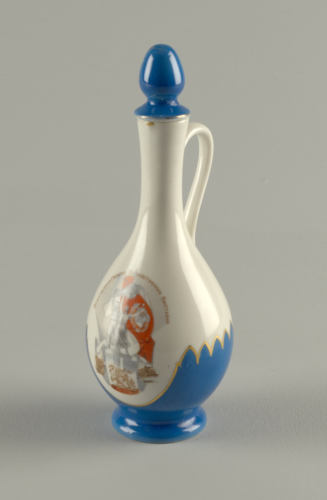 Long tapered neck, bulbous body, flared foot; loop handle; lid with large ovoid finial. Painted with Soviet Emblem of girl and boy holding wheat sheaf aloft and inscription (in Russian); blue border at lower edge and lid painted blue.