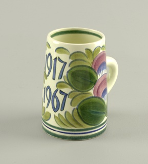 "Cylindrical, slightly narrower towards top, loop handle; polychrome glazed decoration with ""1917/1967"" inscribed opposite handle amid stylized flowers and foliage."
