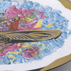 Circular, with notched gilded border and in the center a scene showing a stylized airplane flown by a young man and woman, a red flying carpet, a couple dressed in medieval costume, a chained ogre, caged birds