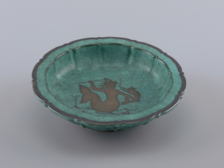 """""""Argenta"""" ware bowl with lobed sides, scalloped edge and circular, molded foot.  Body wall rises in sharp curve to vertical sides, fluted, and flares to broad flat lip.  Silver inlay border at rim of wide band inscribed with chevron pattern and inner plain band.  In center of concave bowl a silver inlay mermaid with upturned tail, holding trident in right hand and stylized swordfish in left.  Below mermaid are silver stylized waves and rising bubbles."""