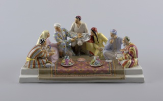 Seven figures sitting on carpet, two plates of fruit resting on carpet (each covers inkwell), front edge of piece steps down to form pen rest; figure on farthest left side in striped robe and cap, woman next to him holds small child, man next to her in patterned robe and white turban, central figure dressed in white, black boots, holds document, next to him a woman in yellow dress, next to her an older man with beard, turban, last figure on right side bearded, dressed in striped robe and cap; base of semi-circular shape, straight side towards front.