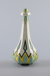 A white vase with a bulbous bottom, ascending into a narrow neck, and a rounded arrow like top. Decorated in a symmetrical pattern of diamonds in black, yellow, and mint green.
