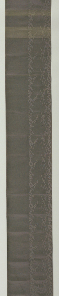Vertically ribbed dark gray silk with a broad band on one with containing stylized elements of pine and bamboo in contrasting weave. Two narrow ribbed selvages. Narrow stripe and three-character inscription woven in gold across one end.