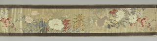 Long horizontal (woven in the vertical and then cut from wide fabric) panel. Ground of cream silk twill. Borders of gold fret design on dark purple twill ground. Design of realistically drawn flowers, including chrysanthemum, iris, peony, lotus, carnation, etc. brocaded in multicolored silks and beaten gold paper wrapped around silk core. Extra weft of beaten gold on flat paper strips forms fret pattern on borders.