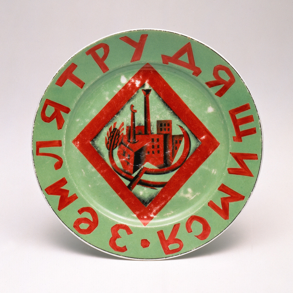 """Circular, green ground with red lettering and image; in the center a lozenge with sickle, wheat sheaf, stylized factory; around the border the slogan in Russian, """"Land for the Working People."""""""