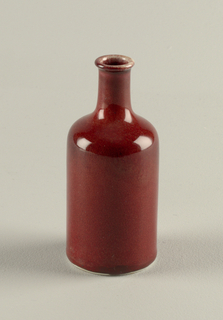 Rectangular shape, with rounded shoulder tapering to long spool neck with slightly flaring rim.  Oxblood colored glaze with ground glaze revealed on rim of neck with unglazed bottom edge and underside.