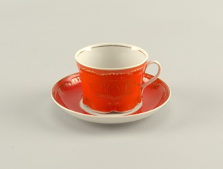 Cup cylindrical, slightly flaring towards top, bottom with scalloped edge, loop handle; painted with gilded inscription on orange enamel background. Saucer circular, raised rim, painted with wide orange border and gilded trim.