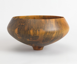 Large thin-walled bowl; wide circular mouth tapering to small circular foot. Form turned from single piece of wood.