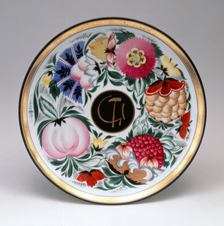 Circular; with hammer, sickle, cog gilded on a black ground in center and a wide border of brightly colored stylized flowers surrounding; gilded outer border
