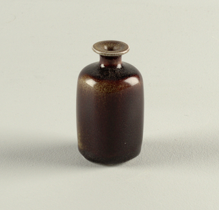Rectangular shape, with rounded sides at shoulder and base.  Flat bottomed; short neck with flaring rim.  Dark brown glaze with areas of ground glaze revealed at shoulder and on one lower side.  Unglazed underside rim and center.