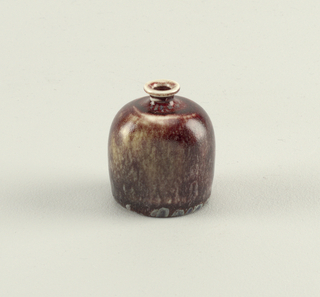 Flat-based, flattened globular shape, rounded shoulder tapering to low neck with flared rim.  Oxblood glaze with splashes of grey-blue glaze near bottom of vase and on rim.  Unglazed foot rim and center on underside.