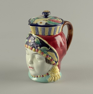 In the form of the head of a woman with elaborate headdress; spout over center face, loop handle back, lid with flattened lobed knob. Polychrome glazed decoration.