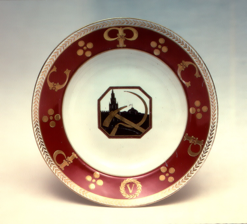 "Circular; in the center an octagonal reserve with silhouette of Kremlin andhammer and sickle; a red border with inscription, in Russian, ""RSFSR,"" a Roman numeral V in a wreath; a gilded leaf outer border"