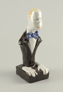 Bust-length figure of man with blond hair, wearing blue bow tie, dark jacket, his hands rest on small square base