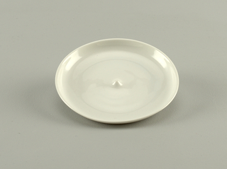 Upturned rimmed saucer with flat base except for a nodule with a slight point that will fit into the indentation in the cup.
