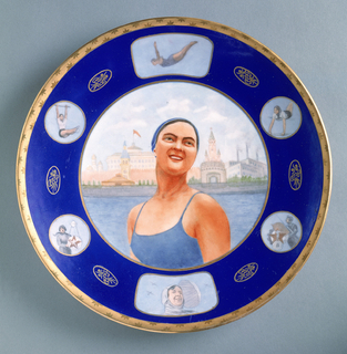 """Large, circular form; in center, image of smiling woman dressed in bathing suit and bathing cap, standing before skyline of Moscow; blue border with six reserves showing women athletes; between each reserve an oval medalion with """"USSR"""" (in Russian) and floral motif; gilded border with burnished star-like pattern."""