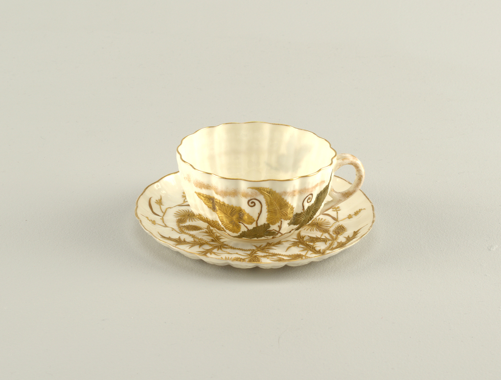 """Extremely thin, transparent white body moulded in ridges resembling a scallop shell. Relief decoration in green and gold.  On cup, a bunch of leaves and a butterfly, on saucer a thistle plant.  Marked """"BELLEEK"""" in rust brown on cup and saucer."""