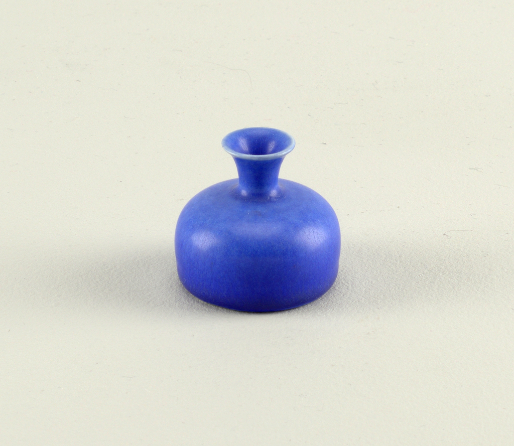 Flat-based vase in form of compressed globe; wide curved shoulder rises to flared spiral neck with flared lips.  Glazed overall in blue, with graded color darkening toward base.  Underside with unglazed foot ring; red-brown matte smear glazed in center.