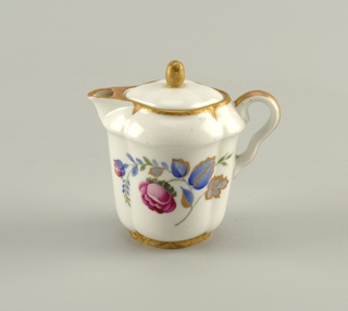 Lobed in form, with double curve handle, short spout, lid with bud-shaped finial; painted with a spray of flowers and leaves in polychrome enamel and gilding