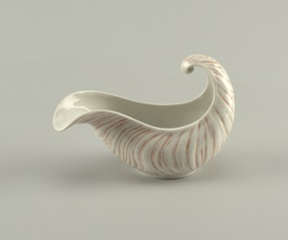 Molded sauceboat in the form of a section of a sea shell with asymmetrical curved lip and upturned shell scroll handle.  Overall striations in gray-rose against white body.