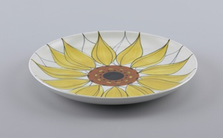 Circular large plate with concave center and raised rim. White body decorated with central medallion of a stylized sunflower with terracotta and black center, yellow and uncolored petals outlined in black.