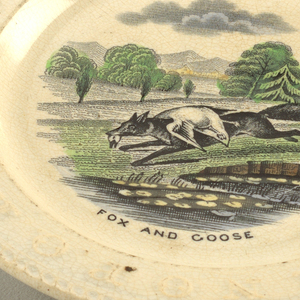 "A and B, with flat marly bearing the alphabet in relief and rope molding on rim. Hand-colored transfer-print of ""Fox and Goose."""