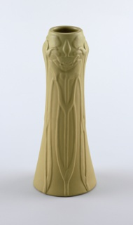 Ochre-colored clay body, cast.  Tall tapering cylindrical body with slightly bulbous shoulder, rises to rim; no foot.  Modeled in low relief around body with three groups of lily triads with the central flower in full bloom at shoulder. Stems extend to base.  Pale gray-yellow matte glaze covers the surface.  Bottom partially glazed.