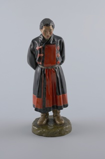 Male figure standing on circular base, his arms joined behind his back.  Wears long overcoat, belted, and boots.  He clasps a cap in his hands.