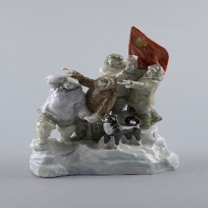 Four men and a dog stand on ice floe, two of the men hold large red banner with gold head of Stalin on it; men dressed in parkas and fur hats.