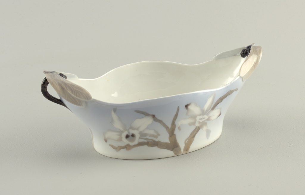 Elongated dish of thin porcelain with painted flowers and applied handles composed of dragonflies.