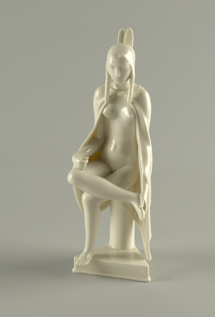 "Female figure, wearing loincloth and holding fan, seated on jar.  Under-glaze mark: waves; overglaze: crown, ""Denmark""; incised: 12468 BL-ch.  Forming a set with 1960-1-59b/e"