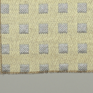Double cloth patterned by metallic silver squares on a cream wool background.