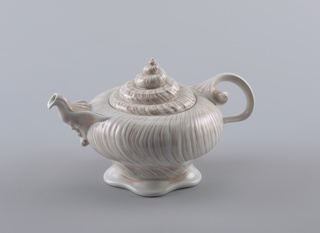 Teapot shaped like a large conch shell, spiral hand, spout in shape of bearded man.